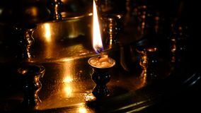 Subtle church candles burn. In an Orthodox Christian church near holy images in the dark in high resolution 4k stock video footage