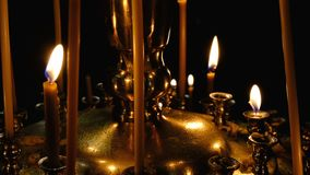 Subtle church candles burn in an Orthodox Christian. Church near holy images in the dark in high resolution 4k stock footage