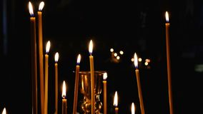 Subtle church candles burn in an Orthodox Christian. Church near holy images in the dark in high resolution 4k stock video footage