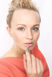 Subtle makeup - blonde paints lips with lipstick Royalty Free Stock Image