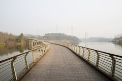 Suburban fenced and planked footbridge over river in sunny winter afternoon. Suburban fenced and planked footbridge over the river in sunny winter afternoon royalty free stock photography