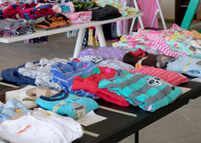 Suburban Garage Sale. A table of colorful children`s pajamas priced and arranged at a garage sale Royalty Free Stock Images