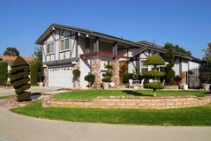 Suburban home. Beautiful suburban house with decorative shrubs and bushes Royalty Free Stock Photo