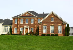 Suburban House. With pine tree and green lawn in front royalty free stock images