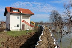 Suburban house protected with flood protection from rising river. Suburban house and surrounding property fully protected with sandbox barrier flood protection royalty free stock image