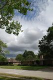 Suburban houses. With green lawns and puffy clouds Stock Photography