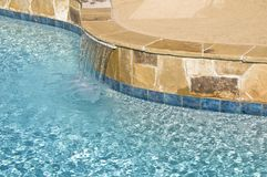Suburban Pool Water Feature. A water feature and flagstone is shown on a suburban pool royalty free stock photos