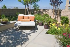 Suburban Retreat. Backyard oasis and suburban retreat with flowers, lounge chair, and patio Stock Photography