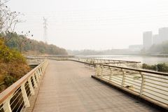 Suburban riverside planked footbridge with benches in sunny winter afternoon. Chengdu,China royalty free stock photo