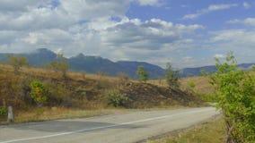 Suburban road through hilly terrain stock footage