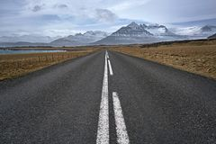 Suburban roadway in Iceland. County roadway between the brown fields with rocks and sea shore on the background of the snow mountains and cloudy sky in Iceland stock photo