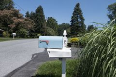 Light blue mailbox on a small town street royalty free stock photography