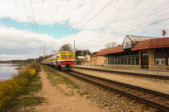 Suburban train arrives at the station near lake Royalty Free Stock Photography