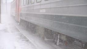 Suburban train arriving. NOVOSIBIRSK REGION, RUSSIAN FEDERATION - JANUARY 5, 2017: Suburban train arriving at the station, snowstorm, slow motion stock video
