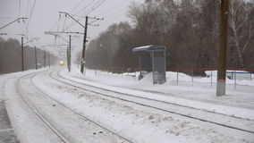 Suburban train arriving. At the station, snowstorm, slow motion stock video