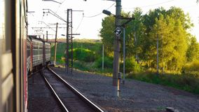 Suburban train at sunset. View from the window of the suburban train, sunset stock footage
