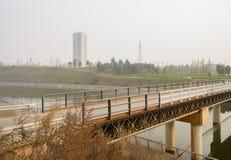 Suburban truss bridge with guardrails across river in sunny winter afternoon. Suburban truss bridge with steel guardrails across the river in sunny winter stock photo