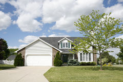 Suburban two-story home. Nice two-story home with brick and vinyl siding with two stall garage, front porch and a big yard Royalty Free Stock Photography