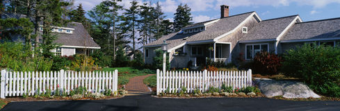 Suburbano-tipo casa com a cerca de piquete branca fotos de stock royalty free