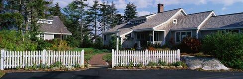 Suburbano-tipo casa con la cerca de piquete blanca Fotos de archivo libres de regalías