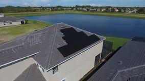 Suburbian domy z energia słoneczna panel na dachach, mała eco wioska z jeziorem, antena strzelali w 4k zdjęcie wideo
