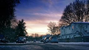 Suburbs In The Snow At Sunset. Moving slowly past houses in the snow with beautiful sunset sky stock video footage