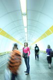 Subway. Young woman standing in a  corridor while the crowd of commuters passes by Stock Photography