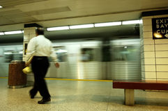 Subway Businessman. A businessman blurred by motion passing by a speeding subway train Royalty Free Stock Images