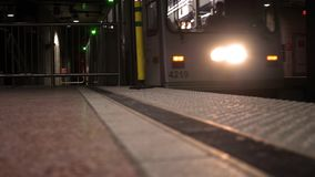 A Subway car arrives at an underground train station at night - low angle. 