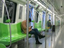 Subway Cars with a Few Passengers. A mostly empty subway car with green seats and a few passengers sitting down royalty free stock images
