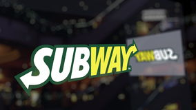 Subway logo on the glass against blurred business center. Editorial 3D rendering Stock Photos