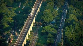 Subway Passing Train Yard And Road Outside City. Train traveling past train yard with old carriages and busy road in golden afternoon sunlight stock footage