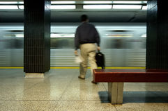 Subway Patron. A subway patron heading towards a subway that's pulling into the station Stock Image
