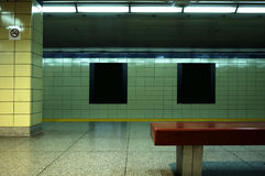 Subway Posters. A vacant subway station with blank subway posters to use for design purposes. Generic no smoking sign and bench in foreground Royalty Free Stock Photo