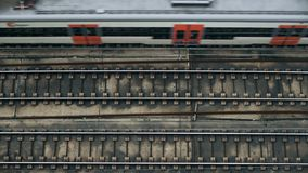 Top view on passing trains. Subway or short distance small train passing by on railroad track at sunny day. Isolated in top of image. Daily commute in town and stock video footage