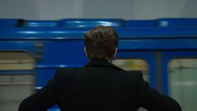 The lonely man waits for someone in a subway. Subway station without a people.The lonely man in a coat nervously waits for someone. the train arrives. Hand held stock footage