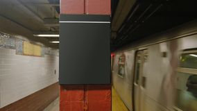 Subway Train Approaches Platform Blank Sign. A New York subway train approaches a platform. Blank sign on pole for easy location identification customization stock video footage