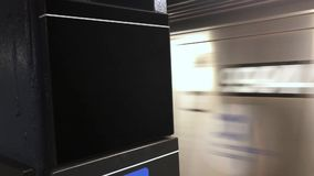 Subway train approaches platform blank sign. A New York subway train approaches a platform. Blank sign on pole for easy location identification customization stock footage