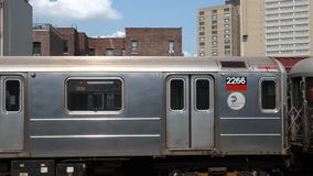 New York City Subway. An out-of-service subway train arrives at above-ground station in Harlem, New York City, makes a pause and leaves stock video