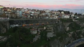 Subway train passing in a tunnel. Twilight view on the bank of the Dora river in Porto. Portugal stock video footage