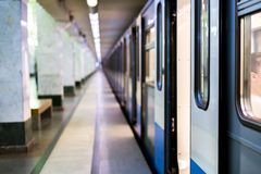Subway train staying on a metro station with doors open with defocused background s Royalty Free Stock Images
