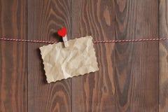 Sucata do papel amarrotado com um clothespeg de madeira com coração vermelho em uma corda Fotos de Stock Royalty Free