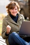 Succeded. Attrractive young woman with laptop making winning gesture
