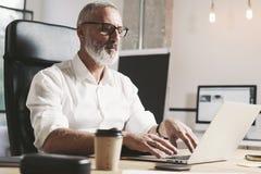 Succes ed uomo d'affari adulto confidenziale facendo uso del computer portatile mobile mentre lavorando alla tavola di legno a mo fotografia stock