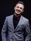 Succes-Kerl in der grauen Jacke, die mit dem Schmetterling lächelt auf dunklem Hintergrund schaut stockbild