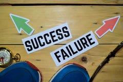 Succes of Mislukking tegenover richtingstekens met tennisschoenen, oogglazen en kompas op houten royalty-vrije stock afbeeldingen