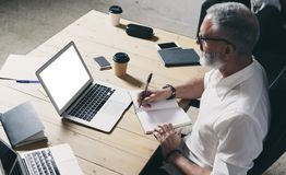 Succes och förtrolig vuxen affärsman som använder den mobila bärbar datordatoren, medan arbeta på trätabellen på modernt Arkivfoto