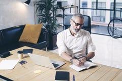Succes och förtrolig vuxen affärsman som använder den mobila bärbar datordatoren, medan arbeta på trätabellen på modernt Arkivbild