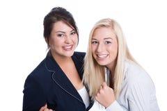 Succes: twee stelden bedrijfsvrouwen tevreden die in bedrijfsuitrusting glimlachen Stock Foto