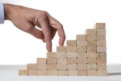 Succesconcept: de treden bouwen met stuk speelgoed houten blokken en menselijke vinger twee beklimmend het op witte achtergrond royalty-vrije stock afbeelding